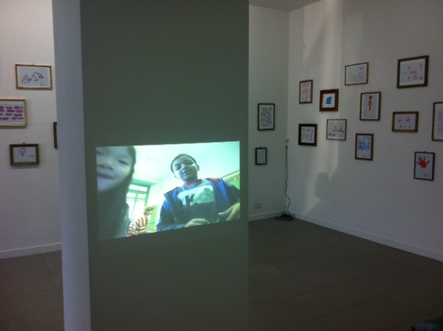 Lingua Mamma, 2013, (with Sara Basta), 2 videos (Fais Dodò, 03:00 - Apo, video loop), drawings made by children,  loudspeakers, installation view at The Gallery Apart Rome