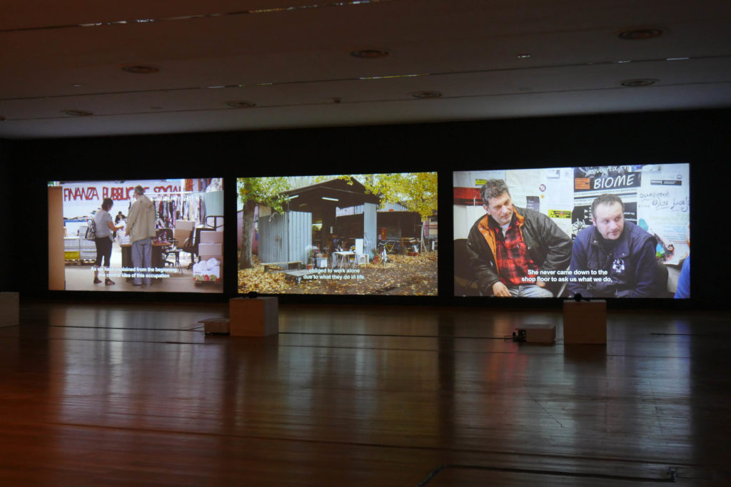"Dario Azzellini & Oliver Ressler, ""Occupy, Resist, Produce"", 3-channel video installation, 2014-2015 (Installation view: ""Property is Theft"", MNAC – National Museum of Contemporary Art, Bucharest, 2016; photo: O. Ressler)"