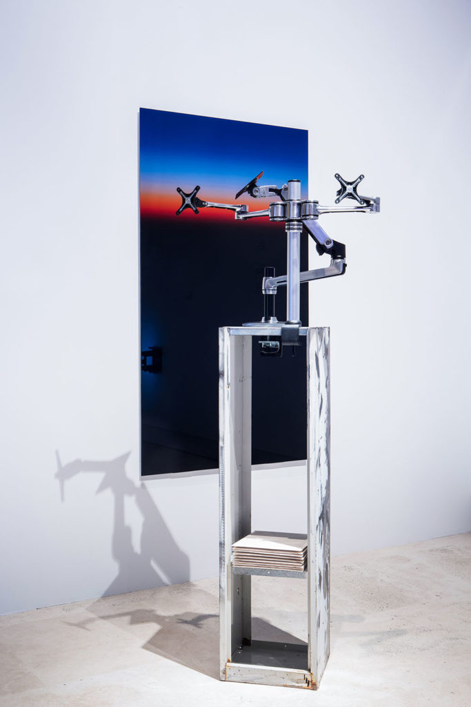 Untitled(Sunset in Utopia), 2015, C-type face mounted on glass, 84,4x150 cm | Apollo and Daphne, 2015, customized locker, 2 desk mount LCD arms, jesmonite sheets, spray paint, filler, size variable. Photo: Gianluca Moscoloni