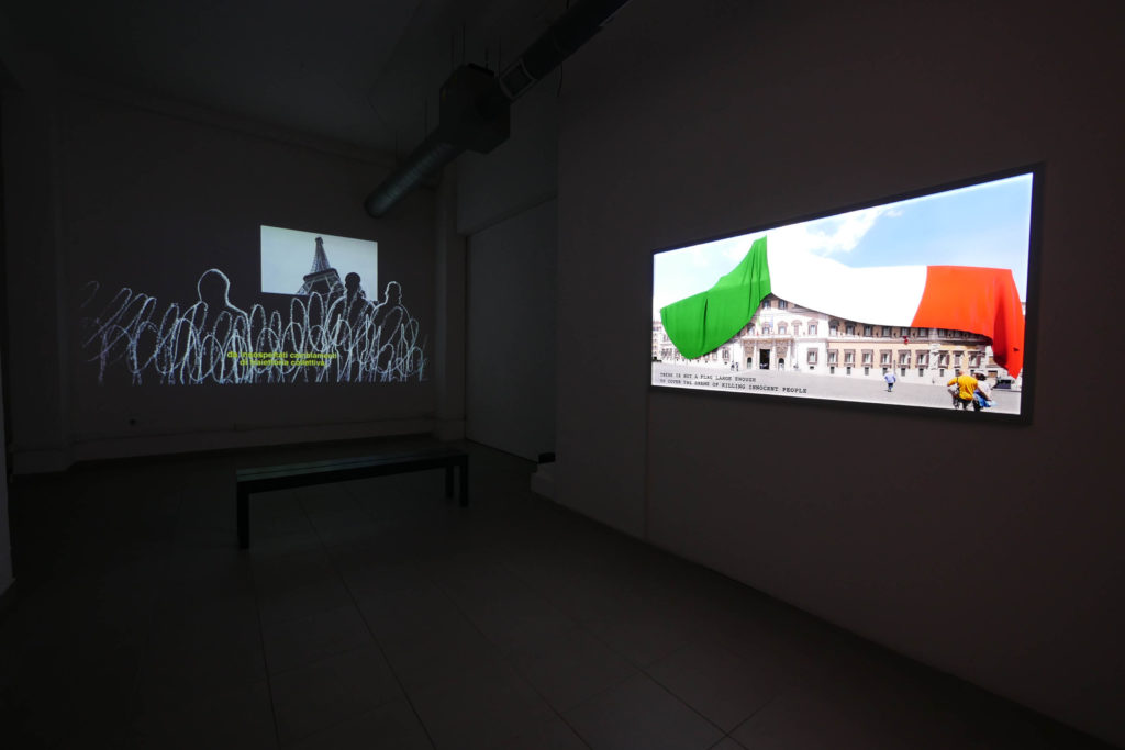 "Oliver Ressler, ""Emergency Turned Upside-Down"", film, 2016; Oliver Ressler, ""There Is Not A Flag"", LED lightbox, 180 x 87 cm, 2016 (Installation view: ""Transnational Capitalism Examined: Border as Method"", The Gallery Apart, Rome, 2016; photo: O. Ressler)"