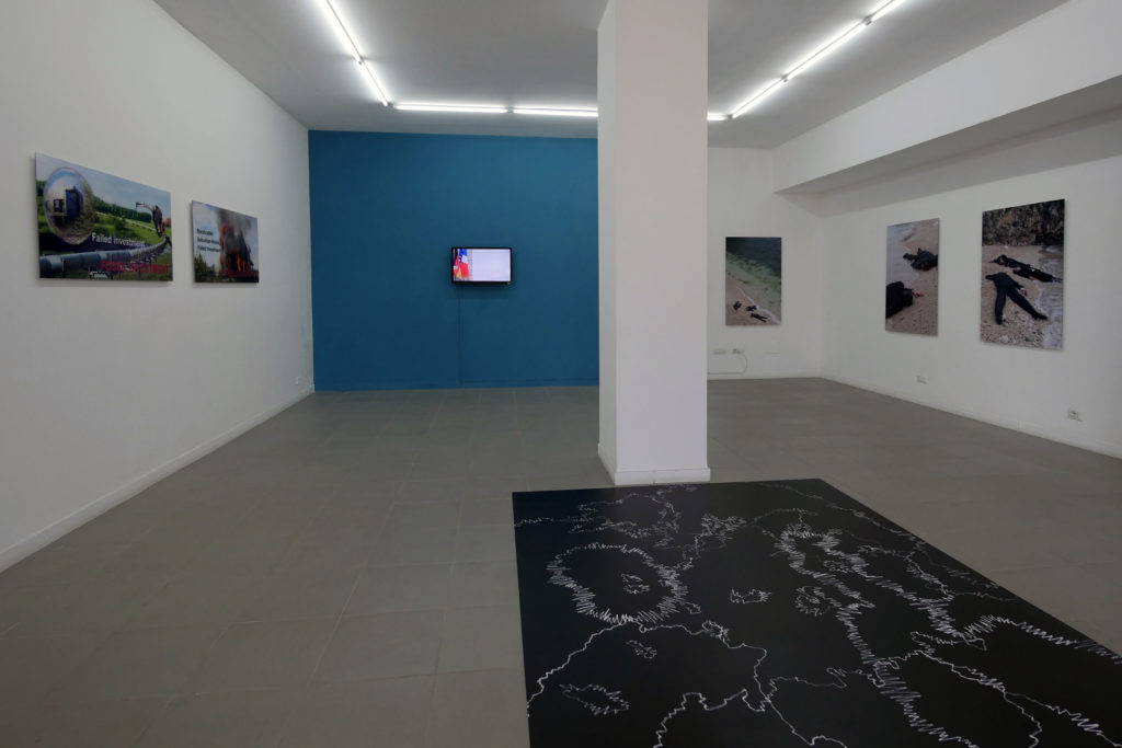 "Oliver Ressler, ""Failed Investments"", digital prints, 120 x 60 cm, 2015; ""Robbery"", film, 2012; ""Stranded"", digital prints, 2015; ""Emergency Turned Upside-Down"", floor piece, 2016 (Installation view: ""Transnational Capitalism Examined: Border as Method"", The Gallery Apart, Rome, 2016; photo: O. Ressler)"
