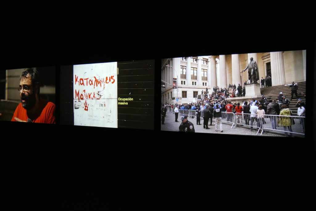 "Oliver Ressler, ""Take The Square"", 3-channel video installation, 2012 (Installation view: ""Playgrounds"", Museo Reina Sofía, Madrid, 2014)"